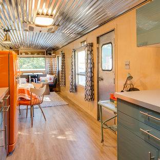 他の地域の小さいミッドセンチュリースタイルのおしゃれなII型キッチン (シングルシンク、フラットパネル扉のキャビネット、青いキャビネット、ステンレスカウンター、カラー調理設備、アイランドなし、ベージュの床、クッションフロア、グレーのキッチンカウンター) の写真
