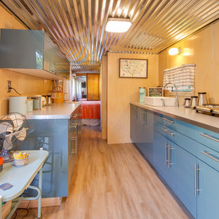 Small mid-century modern kitchen pictures - Small 1960s galley beige floor kitchen photo in Other with flat-panel cabinets, blue cabinets, stainless steel countertops and no island