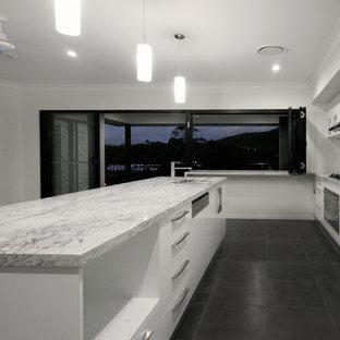 Zweizeilige, Große Moderne Wohnküche mit Unterbauwaschbecken, flächenbündigen Schrankfronten, gelben Schränken, Granit-Arbeitsplatte, Küchenrückwand in Weiß, Glasrückwand, weißen Elektrogeräten, Keramikboden und zwei Kücheninseln in Brisbane