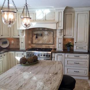 Exempel på ett mellanstort klassiskt beige beige kök, med en undermonterad diskho, luckor med upphöjd panel, granitbänkskiva, beige stänkskydd, en köksö, skåp i slitet trä, stänkskydd i stenkakel, rostfria vitvaror, travertin golv och beiget golv