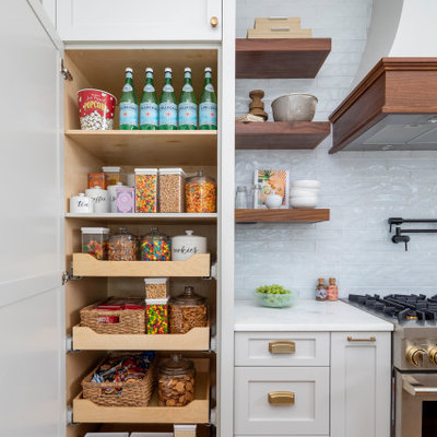 Example of a large beach style l-shaped medium tone wood floor and brown floor kitchen pantry design in Charlotte with a farmhouse sink, gray cabinets, marble countertops, blue backsplash, glass tile backsplash, paneled appliances, an island and white countertops
