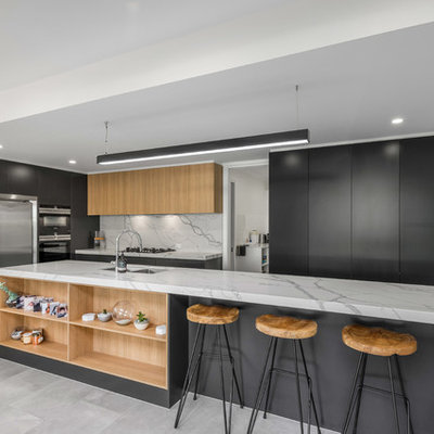 Large trendy galley porcelain tile and gray floor open concept kitchen photo in Brisbane with flat-panel cabinets, gray cabinets, an island, an undermount sink, quartz countertops, white backsplash, stone slab backsplash and stainless steel appliances