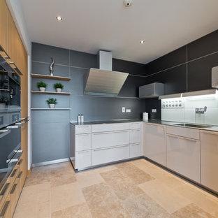 Bild på ett mellanstort, avskilt funkis l-kök, med släta luckor, svart stänkskydd, beiget golv, vita skåp, bänkskiva i rostfritt stål, svarta vitvaror och travertin golv