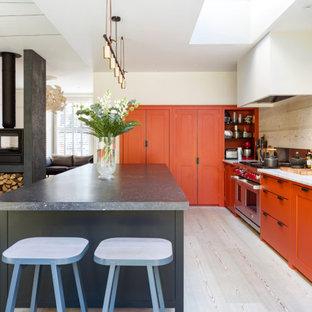 Large contemporary l-shaped kitchen/diner in London with a belfast sink, shaker cabinets, orange cabinets, beige splashback, porcelain splashback, integrated appliances, porcelain flooring, an island, beige floors and white worktops.