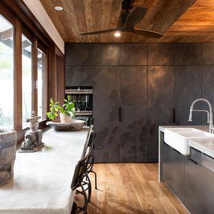 Tropenstil Küche mit Landhausspüle, flächenbündigen Schrankfronten, schwarzen Schränken, braunem Holzboden, Kücheninsel und braunem Boden in Cairns