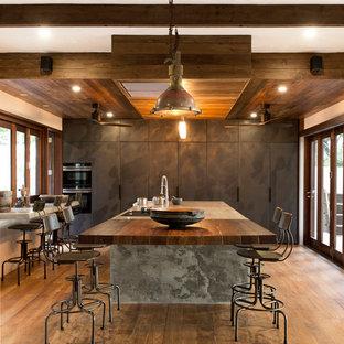 Réalisation d'une cuisine américaine ethnique en L avec un placard à porte plane, des portes de placard marrons, un plan de travail en béton, une crédence en fenêtre, un sol en bois brun, un îlot central, un sol marron et un plan de travail gris.