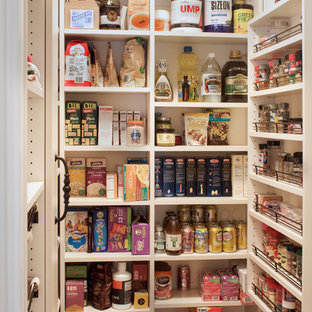 Inspiration for a small rural u-shaped kitchen pantry in New York with a belfast sink, flat-panel cabinets, white cabinets, stainless steel appliances and porcelain flooring.