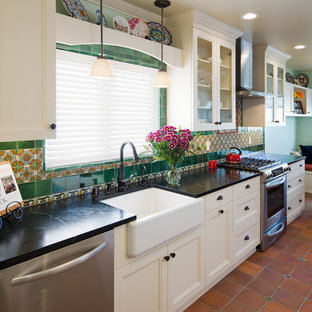 Mid-sized craftsman eat-in kitchen ideas - Inspiration for a mid-sized craftsman single-wall terra-cotta tile eat-in kitchen remodel in San Diego with a farmhouse sink, recessed-panel cabinets, white cabinets, soapstone countertops, green backsplash, ceramic backsplash and stainless steel appliances