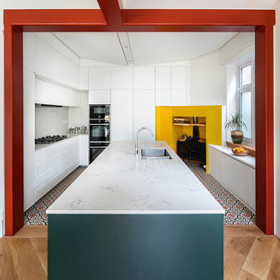 Design ideas for a contemporary u-shaped kitchen in London with a double-bowl sink, flat-panel cabinets, white cabinets, black appliances, ceramic flooring, an island and white worktops.
