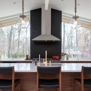 Midcentury single-wall kitchen in Raleigh with an undermount sink, flat-panel cabinets, dark wood cabinets, quartz benchtops, black splashback, ceramic splashback, stainless steel appliances, light hardwood floors, with island and white benchtop.