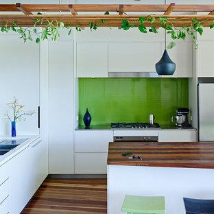 Inredning av ett modernt mellanstort kök, med släta luckor, vita skåp, grönt stänkskydd, stänkskydd i glaskakel, rostfria vitvaror, mellanmörkt trägolv och en köksö