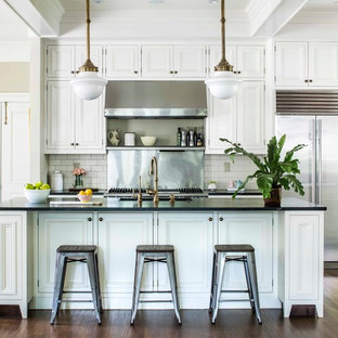 Elegant dark wood floor and brown floor kitchen photo in Atlanta with recessed-panel cabinets, white cabinets, white backsplash, subway tile backsplash, stainless steel appliances, an island and black countertops