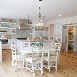 Imagen de cocina comedor clásica con armarios abiertos, puertas de armario blancas, salpicadero gris y electrodomésticos de acero inoxidable