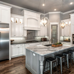 Mid-sized traditional eat-in kitchen ideas - Example of a mid-sized classic l-shaped dark wood floor eat-in kitchen design in Miami with a farmhouse sink, recessed-panel cabinets, white cabinets, gray backsplash, stainless steel appliances, an island, marble countertops and ceramic backsplash