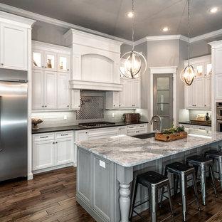 Mittelgroße Klassische Wohnküche in L-Form mit Landhausspüle, Schrankfronten mit vertiefter Füllung, weißen Schränken, Küchenrückwand in Grau, Küchengeräten aus Edelstahl, dunklem Holzboden, Kücheninsel, Marmor-Arbeitsplatte und Rückwand aus Keramikfliesen in Miami