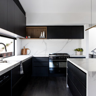 Contemporary l-shaped kitchen in Wollongong with a double-bowl sink, flat-panel cabinets, black cabinets, white splashback, panelled appliances, painted wood floors, with island, black floor and white benchtop.