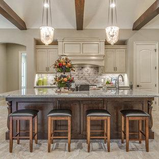 Große Mediterrane Wohnküche in L-Form mit beigen Schränken, Küchenrückwand in Beige, Kücheninsel, beigem Boden, Granit-Arbeitsplatte, Unterbauwaschbecken, Schrankfronten mit vertiefter Füllung, Rückwand aus Keramikfliesen, Küchengeräten aus Edelstahl und Keramikboden in Houston