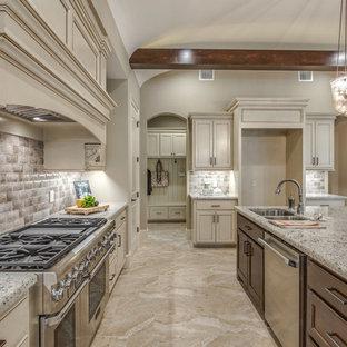 Große Mediterrane Wohnküche in L-Form mit Unterbauwaschbecken, Schrankfronten mit vertiefter Füllung, weißen Schränken, Granit-Arbeitsplatte, Küchenrückwand in Beige, Rückwand aus Keramikfliesen, Küchengeräten aus Edelstahl, Keramikboden, Kücheninsel und beigem Boden in Houston