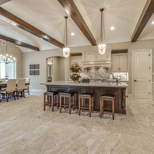 Große Mediterrane Wohnküche in L-Form mit Schrankfronten mit vertiefter Füllung, weißen Schränken, Granit-Arbeitsplatte, Küchenrückwand in Beige, Rückwand aus Keramikfliesen, Küchengeräten aus Edelstahl, Kücheninsel, Unterbauwaschbecken, Keramikboden und beigem Boden in Houston