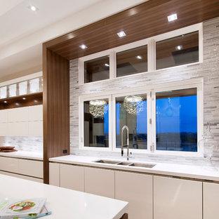 カルガリーの大きいコンテンポラリースタイルのおしゃれなキッチン (トリプルシンク、フラットパネル扉のキャビネット、白いキャビネット、珪岩カウンター、マルチカラーのキッチンパネル、ボーダータイルのキッチンパネル、シルバーの調理設備の、濃色無垢フローリング) の写真