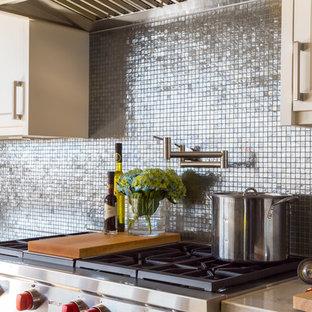 Immagine di una grande cucina classica con lavello sottopiano, ante in stile shaker, paraspruzzi a effetto metallico, paraspruzzi con piastrelle di metallo, elettrodomestici in acciaio inossidabile, pavimento in legno massello medio, isola, ante bianche e top in superficie solida