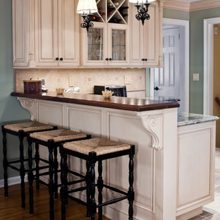 Inspiration for a mid-sized traditional u-shaped eat-in kitchen in New York with an undermount sink, beige cabinets, granite benchtops, beige splashback, stainless steel appliances, ceramic floors, a peninsula, raised-panel cabinets and porcelain splashback.
