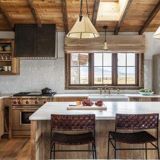 Inredning av ett rustikt l-kök, med en rustik diskho, öppna hyllor, skåp i mellenmörkt trä, vitt stänkskydd, rostfria vitvaror, mellanmörkt trägolv och en köksö