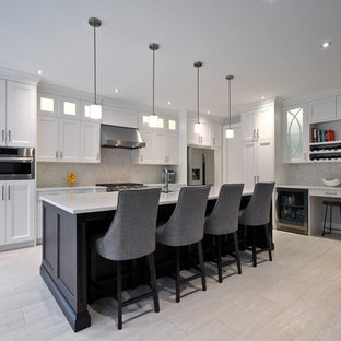 Inspiration for a large transitional l-shaped open plan kitchen in Toronto with an undermount sink, shaker cabinets, white cabinets, solid surface benchtops, multi-coloured splashback, mosaic tile splashback, stainless steel appliances, porcelain floors, with island and beige floor.