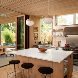 Design ideas for a midcentury kitchen in Denver with an integrated sink, open cabinets, stainless steel benchtops, metallic splashback, stainless steel appliances, light hardwood floors and with island.