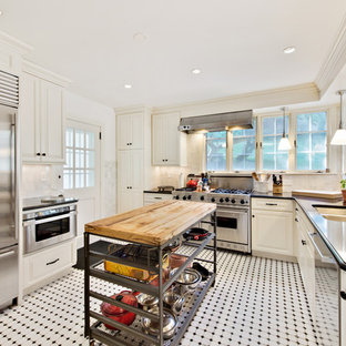 Traditional kitchen ideas - Inspiration for a timeless l-shaped kitchen remodel in Denver with a double-bowl sink, raised-panel cabinets, white cabinets, white backsplash, stainless steel appliances and an island