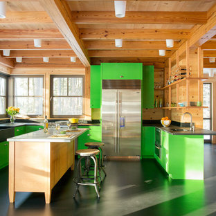 Photo of a country u-shaped eat-in kitchen in Boston with a farmhouse sink, flat-panel cabinets, green cabinets, brown splashback, timber splashback, stainless steel appliances, with island, black floor and black benchtop.