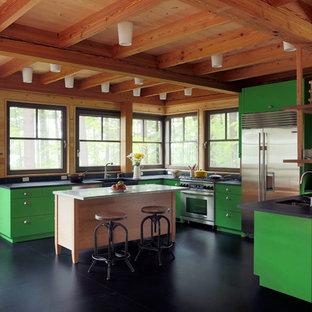 ボストンの中サイズのエクレクティックスタイルのおしゃれなキッチン (エプロンフロントシンク、フラットパネル扉のキャビネット、緑のキャビネット、シルバーの調理設備の、人工大理石カウンター、コンクリートの床、黒い床) の写真