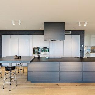 Immagine di una grande cucina minimal con lavello a doppia vasca, ante lisce, ante in legno bruno, elettrodomestici in acciaio inossidabile, parquet chiaro, isola, top in quarzo composito e pavimento beige