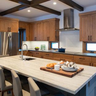他の地域の中サイズのラスティックスタイルのおしゃれなキッチン (シングルシンク、シェーカースタイル扉のキャビネット、珪岩カウンター、白いキッチンパネル、磁器タイルのキッチンパネル、シルバーの調理設備の、コンクリートの床、グレーの床、白いキッチンカウンター、中間色木目調キャビネット) の写真