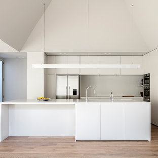 Minimalist galley eat-in kitchen photo in Melbourne with gray backsplash, stainless steel appliances, an island, flat-panel cabinets and white cabinets