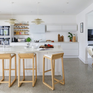 Inspiration for a medium sized contemporary galley kitchen in Cornwall with a double-bowl sink, flat-panel cabinets, white cabinets, white splashback, an island, grey floors, white worktops and stainless steel appliances.