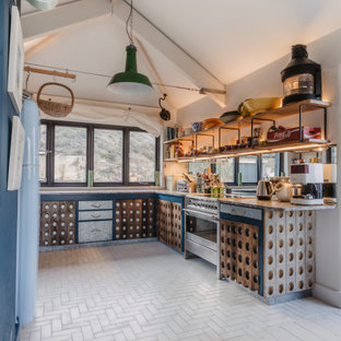 Medium sized coastal u-shaped kitchen in Cornwall with marble worktops, cement flooring, no island, white floors, black worktops, medium wood cabinets and a vaulted ceiling.
