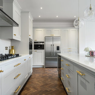 Inspiration for a medium sized traditional u-shaped open plan kitchen in London with an integrated sink, shaker cabinets, grey cabinets, quartz worktops, white splashback, stainless steel appliances, laminate floors, an island, brown floors and stone slab splashback.