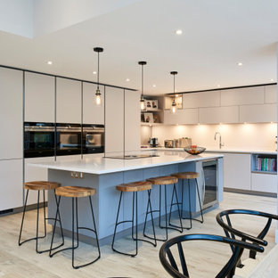 Design ideas for a large contemporary l-shaped eat-in kitchen in Hertfordshire with flat-panel cabinets, grey cabinets, solid surface benchtops, ceramic floors, with island, white benchtop, black appliances and beige floor.