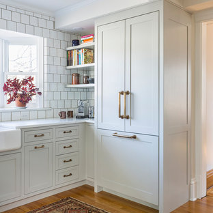ミネアポリスの大きいトランジショナルスタイルのおしゃれなキッチン (フラットパネル扉のキャビネット、グレーのキャビネット、大理石カウンター、白いキッチンパネル、セメントタイルのキッチンパネル、シルバーの調理設備の、淡色無垢フローリング、アイランドなし、茶色い床) の写真