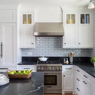 Geschlossene, Mittelgroße Klassische Küche in U-Form mit Unterbauwaschbecken, weißen Schränken, Küchenrückwand in Grau, Rückwand aus Metrofliesen, Küchengeräten aus Edelstahl, Kücheninsel, flächenbündigen Schrankfronten, Speckstein-Arbeitsplatte und braunem Holzboden in Minneapolis