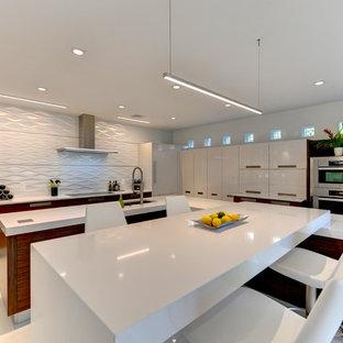 Große Moderne Wohnküche in L-Form mit flächenbündigen Schrankfronten, hellbraunen Holzschränken, Mineralwerkstoff-Arbeitsplatte, Küchenrückwand in Weiß, Küchengeräten aus Edelstahl, Keramikboden, Halbinsel und weißem Boden in Sonstige