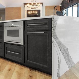 Idéer för stora lantliga gult kök, med en rustik diskho, luckor med glaspanel, vita skåp, bänkskiva i kvarts, vitt stänkskydd, stänkskydd i keramik, rostfria vitvaror, ljust trägolv, en köksö och brunt golv