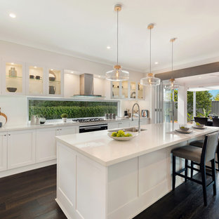 This is an example of a mid-sized contemporary galley eat-in kitchen in Sydney with shaker cabinets, white cabinets, quartz benchtops, white splashback, dark hardwood floors, with island, brown floor, white benchtop and an undermount sink.