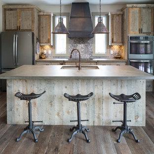 Idées déco pour une cuisine montagne avec un évier encastré, une crédence multicolore, un électroménager en acier inoxydable, un sol en bois foncé et un îlot central.