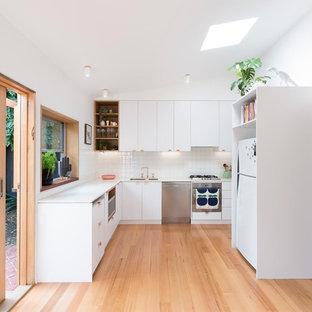 Kleine Skandinavische Küche mit weißen Schränken, Arbeitsplatte aus Terrazzo, Küchenrückwand in Weiß, Rückwand aus Keramikfliesen, hellem Holzboden und weißer Arbeitsplatte in Melbourne