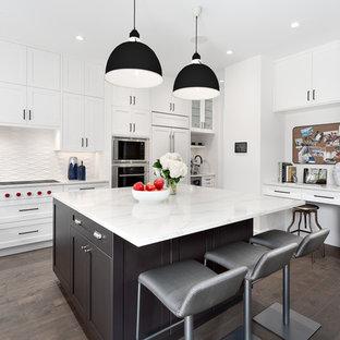 Klassisk inredning av ett stort vit vitt l-kök, med vita skåp, bänkskiva i kvarts, vitt stänkskydd, stänkskydd i porslinskakel, en köksö, brunt golv, skåp i shakerstil, integrerade vitvaror och mörkt trägolv