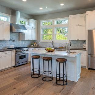 Exemple d'une cuisine ouverte chic en L avec un évier de ferme, un placard à porte shaker, des portes de placard blanches, une crédence multicolore, une crédence en carreau briquette, un électroménager en acier inoxydable, un sol en bois brun, un îlot central, un sol marron et un plan de travail multicolore.
