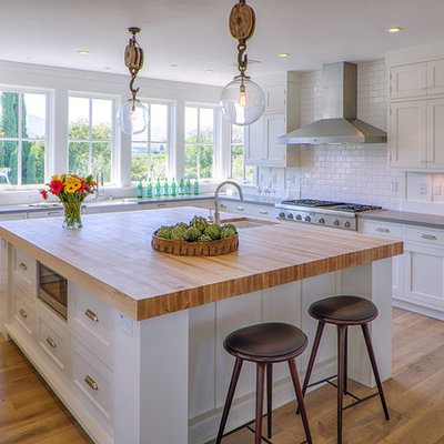 Example of a farmhouse u-shaped medium tone wood floor kitchen design in San Francisco with an undermount sink, shaker cabinets, white cabinets, white backsplash, subway tile backsplash, stainless steel appliances and an island