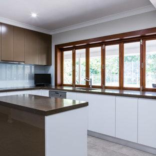 シドニーの広いモダンスタイルのおしゃれなキッチン (アンダーカウンターシンク、白いキャビネット、クオーツストーンカウンター、黄色いキッチンパネル、ガラス板のキッチンパネル、シルバーの調理設備、セラミックタイルの床) の写真